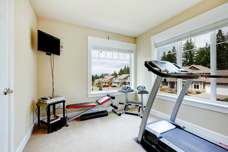 Home gym with equipment, weights and TV with two large windows.