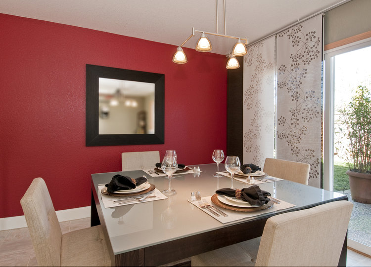 modern dining room with glass top table, red wall with mirror, place settings, window shades, overhead lighting